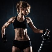 stock photo of bandage  - Brutal athletic woman pumping up muscules with barbell - JPG