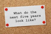 foto of goal setting  - The question What Do The Next Five Years Look Like typed on a piece of graph paper and pinned to a cork notice board - JPG