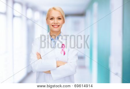 healthcare and medicine concept - smiling female doctor with pink cancer awareness ribbon over hospital background