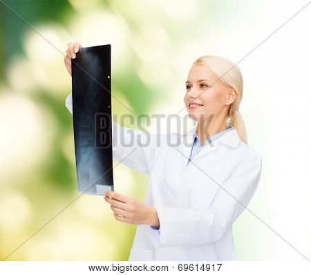 healthcare, medicine and radiology concept - smiling female doctor looking at x-ray over natural background