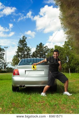 Excited Male Holding Licence Permit Plates Beside Silver Car