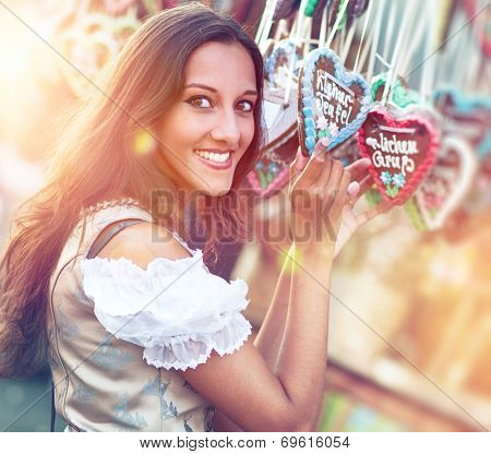 Young beautiful woman in Dirndl costume together with German Gingerbread heart