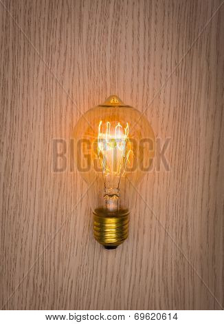 Glowing bulb on the wooden table