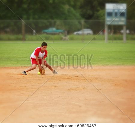 a woman squatting down to catch a grounder in a softball game