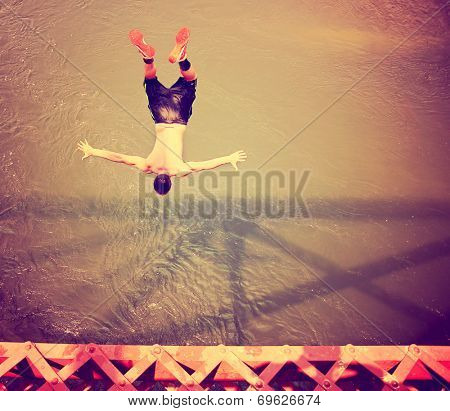 a boy jumping of an old train trestle bridge into a river toned with a retro vintage instagram filter