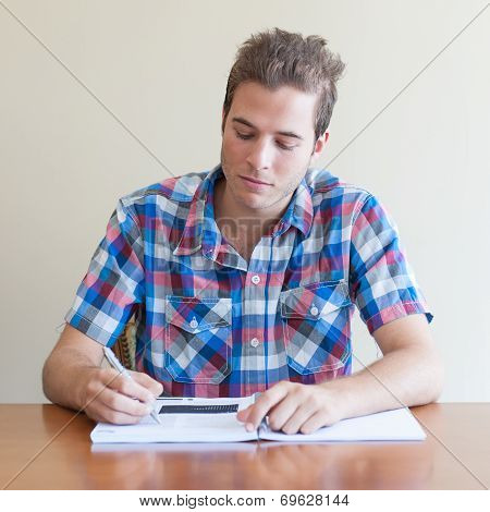 Young Adult Studying With A Book And A Pen