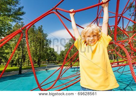 Positive boy with straight hands hangs on rope