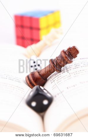 CHESS PIECE WITH DICE ON A BOOK AND RUBIK'S CUBE