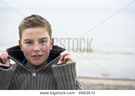 Young Handsome Boy With Pullover At Beach In Winter Time