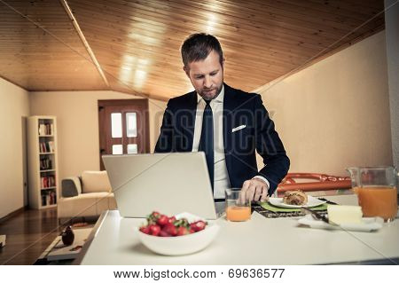 Businessman working at PC home during breakfast