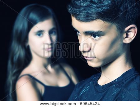 Unhappy young teen couple - boy and girl - on a black background