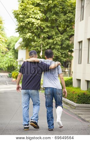 Friend Helping Brothers Or Patient  To Walk Without Crutches