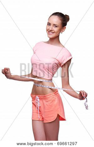 Woman measuring her waist with a measuring tape