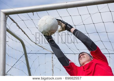 Goalkeeper in red jumping up to save a goal on a clear day