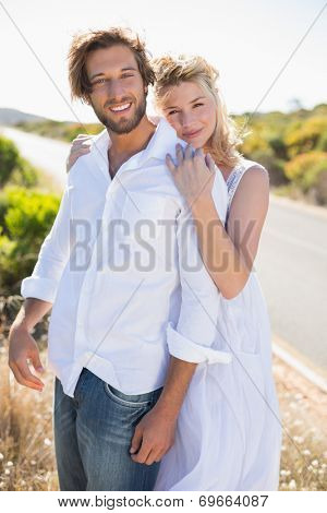 Attractive couple smiling at camera road side on a sunny day