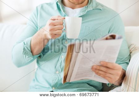 home, rest, news, drinks and people concept - close up of man reading magazine and drinking from cup sitting on couch at home