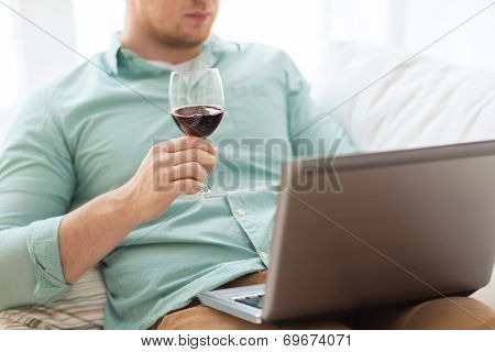 technology, drinks, leisure, home and lifestyle concept - close up of man close up of man with laptop and glass of wine at home