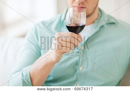 drinks, relax, leisure and people concept - close up of man drinking red wine and sitting on couch at home