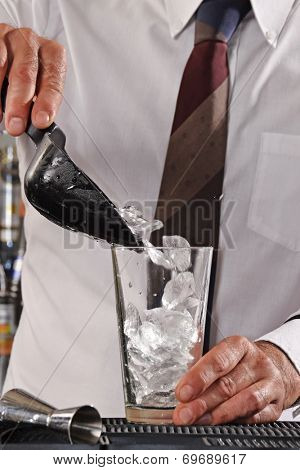 Barman pouring ice cubes on cocktail glass.Bartender preparing cocktail drink.