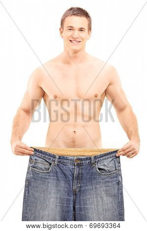Shirtless weightloss male showing his old pair of jeans, isolated on white background