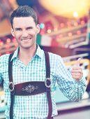 stock photo of lederhosen  - Beautiful man wearing traditional Bavarian Lederhosen doing thumbs up - JPG
