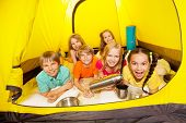 picture of thermos  - Six funny children laying in the yellow camping tent with thermos and aluminum cups - JPG