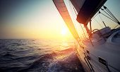 stock photo of rudder  - Sail boat gliding in open sea at sunset - JPG