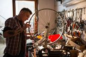 stock photo of adults only  - Young man working in a biking repair shop - JPG