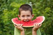 stock photo of watermelon slices  - Kid eating red ripe watermelon - JPG