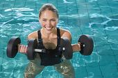 foto of day care center  - Fit blonde working out with foam dumbbells in swimming pool at the leisure centre - JPG