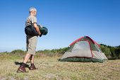 picture of sleeping bag  - Happy camper walking towards his tent holding sleeping bag on a sunny day - JPG