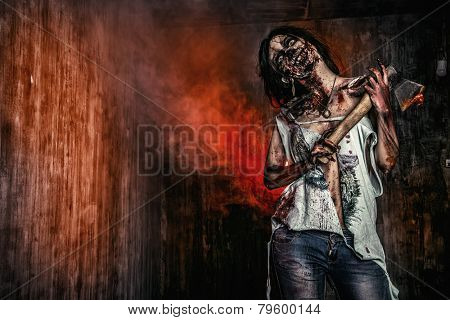 Scary bloody zombie girl with an ax. Halloween.