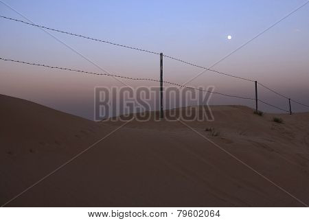 Fence of barbed wire in the desert.