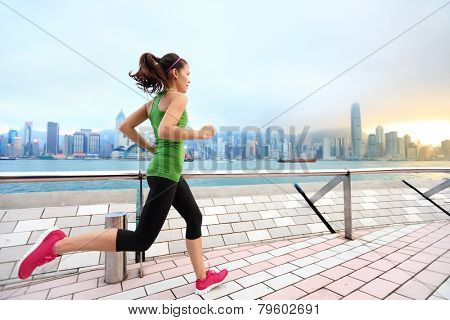 City Running - woman runner and Hong Kong skyline. Female athlete fitness athlete jogging training living healthy lifestyle on Tsim Sha Tsui Promenade and Avenue of Stars in Victoria Harbour, Kowloon.