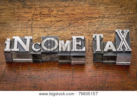 income tax - financial concept - words in mixed vintage metal type printing blocks over grunge wood