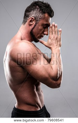 Portrait of a muscular man keeping his palms by face