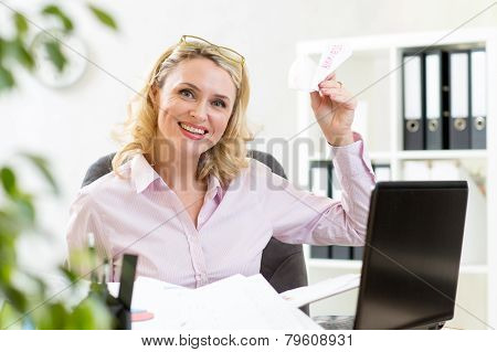 businesswoman throwing paper airplane in office