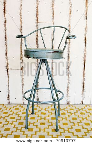 Vintage Stool With White Wooden Background.