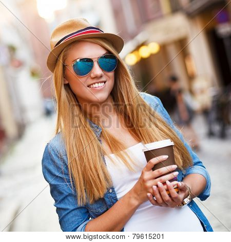 Young stylish woman drinking coffee to go in a city street