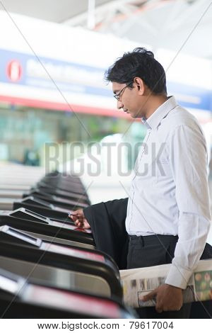 Asian Indian businessman at entrance of railway station, touching ticket token on gate barrier.