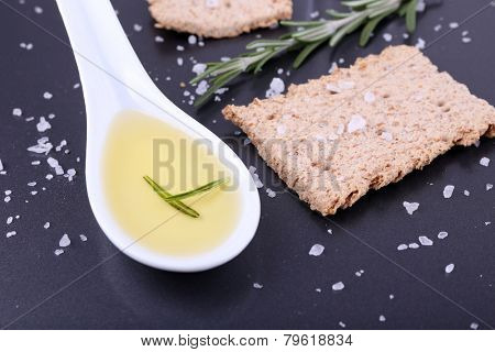 Crispbread with salt, spoon of oil and sprigs of rosemary on color table background