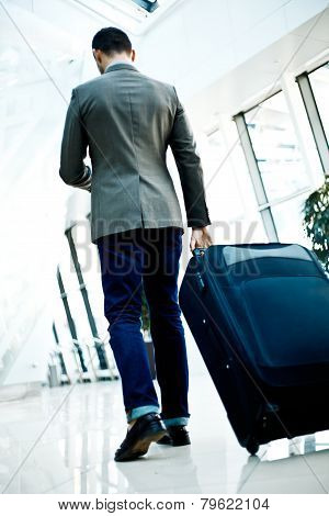 Rear View Of Businessman Carrying Luggage Walk Toward Escalator In Airport Hall