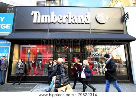 NEW YORK CITY - MONDAY, DEC. 29, 2014: Pedestrians walk past a Timberland shoe anc clothing store.  Timberland LLC is an American manufacturer and retailer of outdoors wear with a focus on footwear