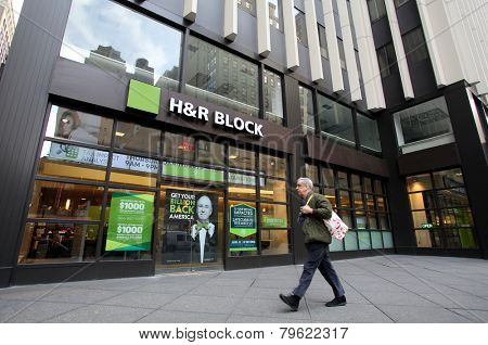 NEW YORK CITY - MONDAY, DEC. 29, 2014: Pedestrians walk past an office of H&R Block. H&R Block is a tax preparation company in the United States
