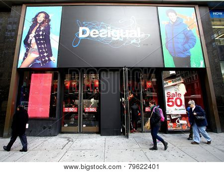 NEW YORK CITY - MONDAY, DEC. 29, 2014: Pedestrians walk past a Desigual clothing store. Desigual is a casual clothing brand based in Barcelona, Spain