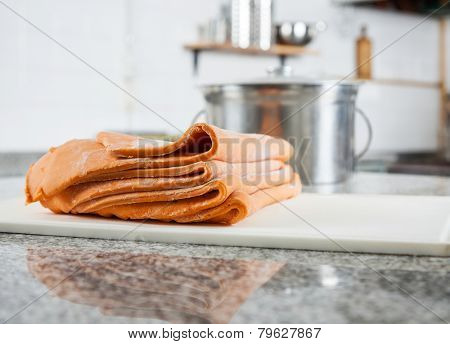 Folded ravioli pasta sheets on cutting board at countertop in commercial kitchen