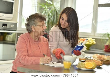 Homecare helping elderly woman doing crossword