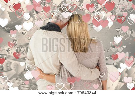 Happy couple standing with arms around against grey valentines heart pattern