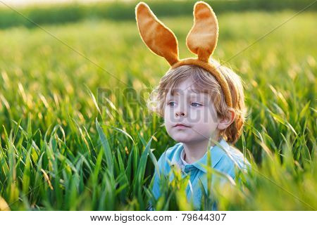 Cute Little Child With Easter Bunny Ears Playing In Green Grass