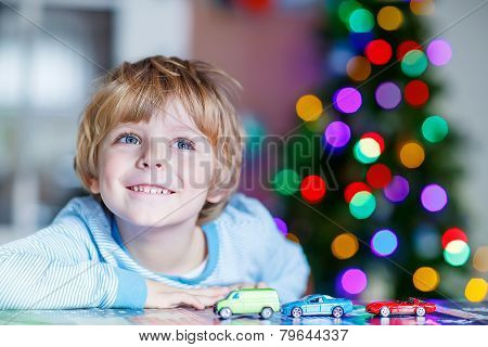 Little Blond Child Playing With Cars And Toys At Home